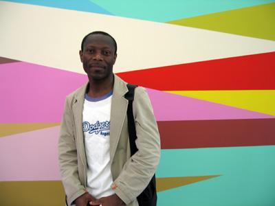 Olu Oguibe (atrás uma pintura mural de Odili Donald Odita). Foto de Christine Eyene.