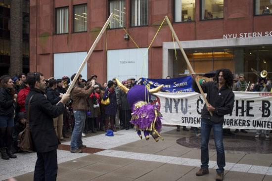 "NYU4OWS, Wally, November 17, 2011. ""The Spirit of Occupy Wall Street at NYU"" bull piñata performance, New York (Stern School of Business, New York University). Courtesy Daniel Aldana Cohen."