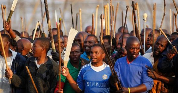 16 agosto 2012, mineiros em greve reúnem-se em área de mina da produtora de platina Lonmin, em Marikana, na África do Sul. A polícia abriu fogo contra os mineiros.