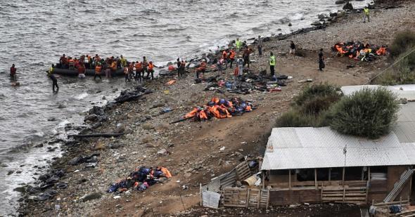 Bote com refugiados chega a ilha de Lesbo, na Grécia, após cruzar o mar Egeu desde a Turquia.