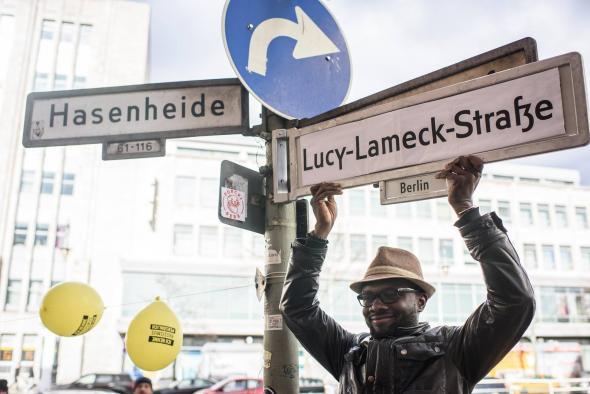 Abdel Amine Mohammed segura uma sinalética alternativa que honra o político tanzaniano Lucy Lameck. fogorafia de Daniel Rodriguez