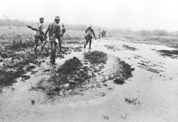 Guerrilheiros do PAIGC atravessando uma bolanha, interior da Guiné. 1963 - 1973