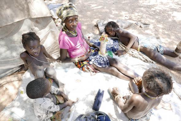 Madukilaxi rodeada pelas duas filhas mais novas e netos, terminando outra boneca a pedido, 2018