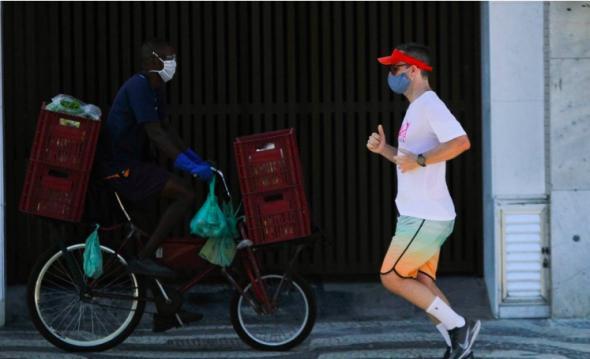 Trabalhador precarizado carrega alimentos enquanto o morador faz exercícios.