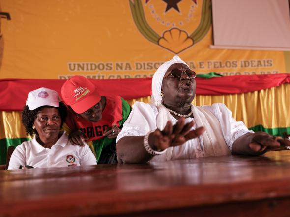 Bissau, Guinea Bissau (March 8, 2019) – Bilony Nhama (left, white shirt) is the Secretary General for the Women's Democratic Union for the PAIGC party. She sits next to Teodora Gomes (far right), who is a hero of the country's independence war. Here in Guinea Bissau, the women gather for an event on International Women's Day, two days before legislative elections where a new law required that 36 % of candidates be women. Image credit Ricci Shryock.