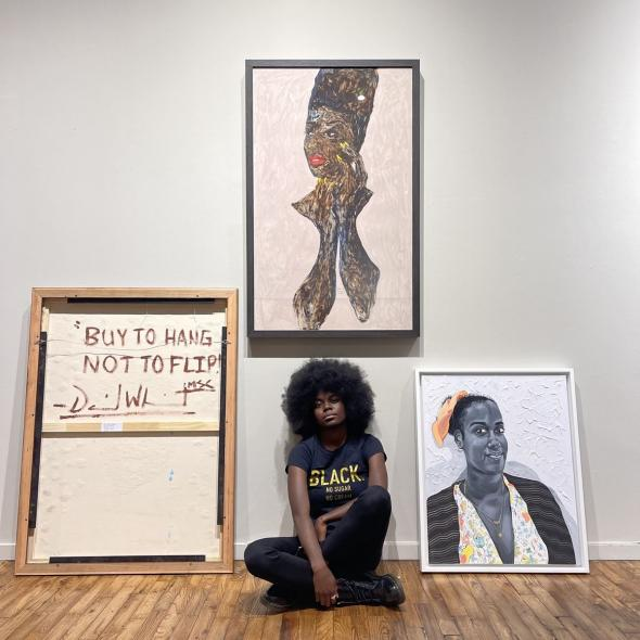 Portrait of Destinee Ross-Sutton with, from left to right, works by David 'Mr. StarCity' White (showing the back of the work), Amoako Boafo, and Otis Kwame Kye Quaicoe, from the exhibition 'Black Voices- Friend of My Mind.' Courtesy of Destinee Ross-Sutton.