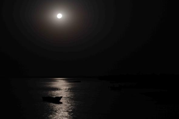 Lua cheia sobre os barcos do rio Cachéu