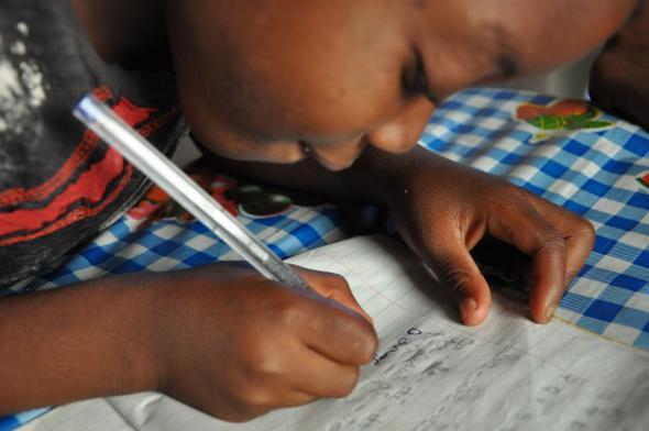 Dércio, de 9 anos, perdeu os avós e cresceu num agregado chefiado por crianças. O tio cuida dele como um pai.