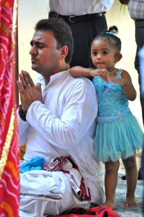 Nitin, sacerdote do templo de Maputo, conduzindo sentado as cerimónias de aniversário do templo, a 8 de Maio, com a filha Nandini sempre por perto