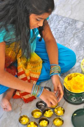 uma jovem hindu prepara velas artesanais antes de uma cerimónia religiosa no templo de Maputo