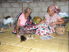 D. Maria Macuácua, ensinando a leitura do tinhlolo a uma das suas filhas de espíritos (foto de Paulo Granjo)