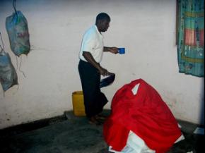 Eng Job Massinge, administrando um bafo a um paciente. Segura na mão o tchova, instrumento essencial do kufemba de xizingo (foto de Cremildo Binana)